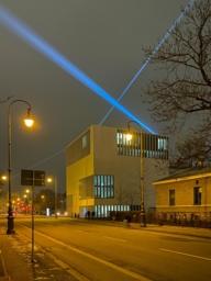 Von den Dächern des Kunstareals München scheinen riesige Lichtstrahlen von Dach zu Dach und verbinden die Museen des Kunstareals.