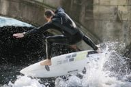 At the Eisbach bridge there are spectators day and night watching the surfers riding the waves.