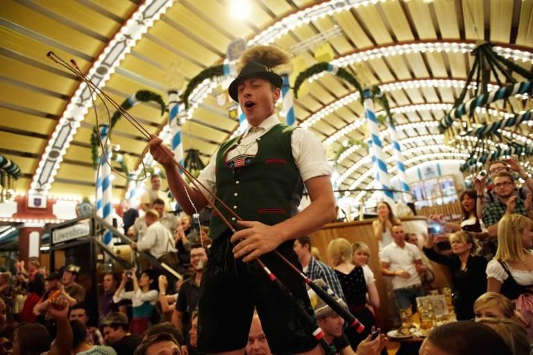 Ein Trachtler feiert ausgelassen in einem Bierzelt des Oktoberfestes in München.