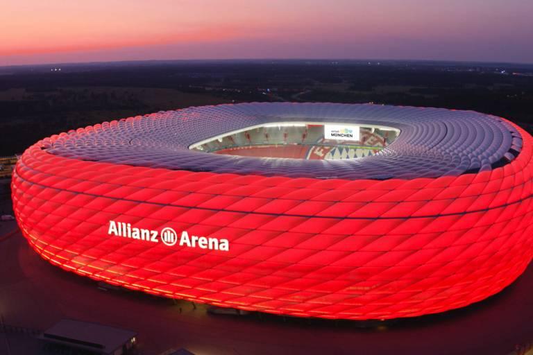 Allianz Arena in rot beleuchtet bei Abend.