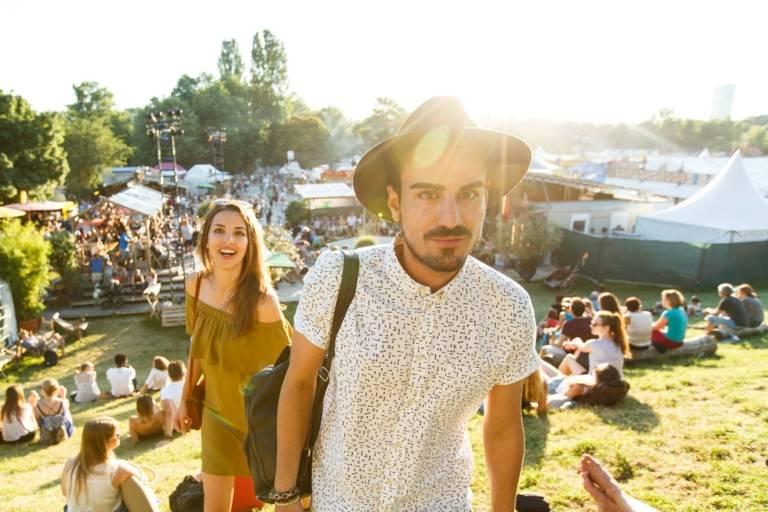 Ein junges Paar auf einem kleinen Berg mit Liegewiese auf dem Tollwood Festival in München.
