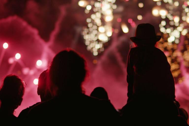 Menschen betrachten ein funkelndes Feuerwerk in München