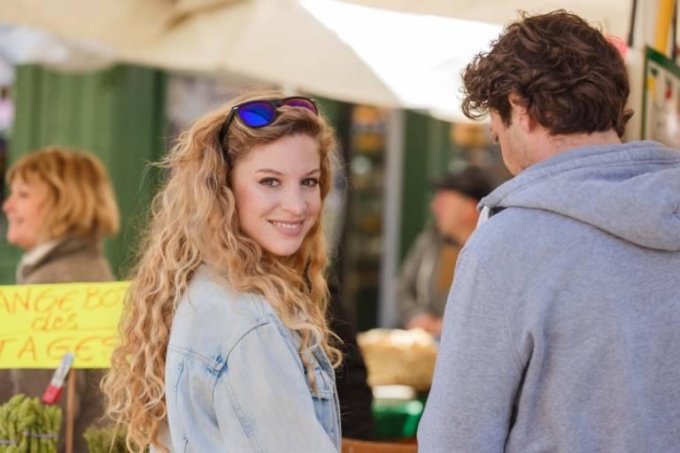 Eine Frau steht lächelnd an einem Stand auf dem Viktualienmarkt in München.
