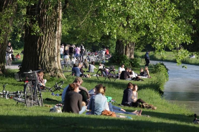 Menschen sitzen am Ufer des Eisbachs im Englischen Garten in München.