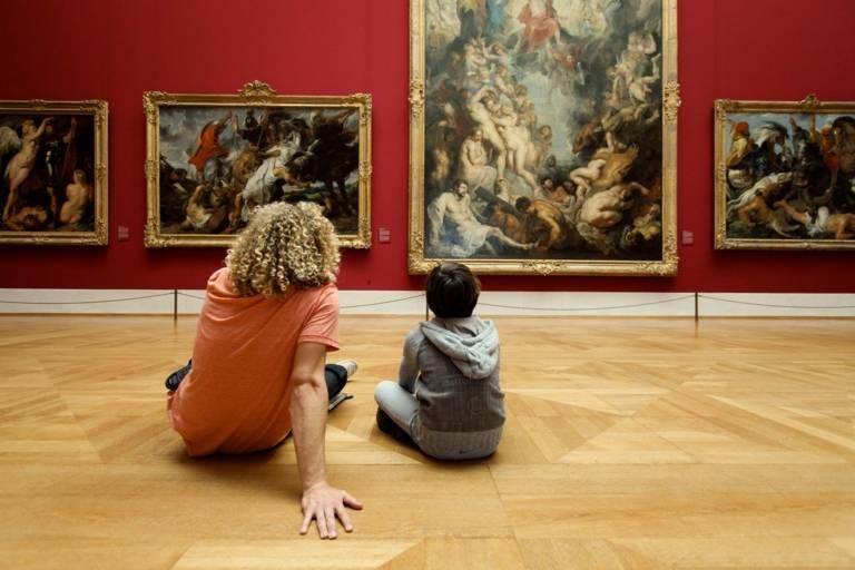Ein junger Mann und ein Junge sitzen auf dem Boden des Rubensaals der Alten Pinakothek in München und betrachten Gemälde.