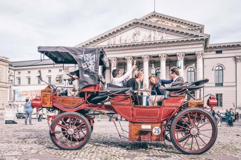 Eine rote Kutsche steht auf dem Max-Jospeh-Platz in München