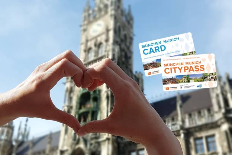 Zwei Hände formen ein Herz, im Hintergrund der Turm des Neuen Rathauses am Marienplatz in München.