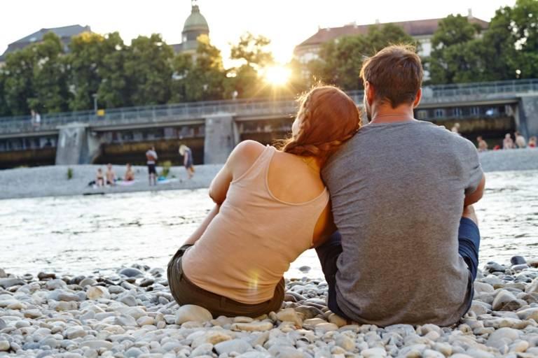 Ein Paar sitzt, dem Wasser zugewandt, an der Isar in München.