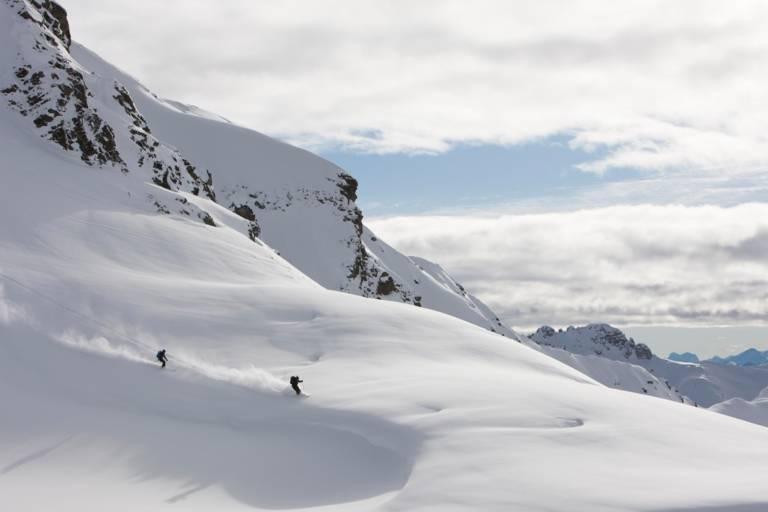 Zwei Skifahrer bei der Abfahrt im Tiefschnee vor Bergpanorama.