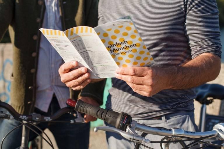 Ein Mann mit Fahrrad hält einen München-Prospekt in der Hand.
