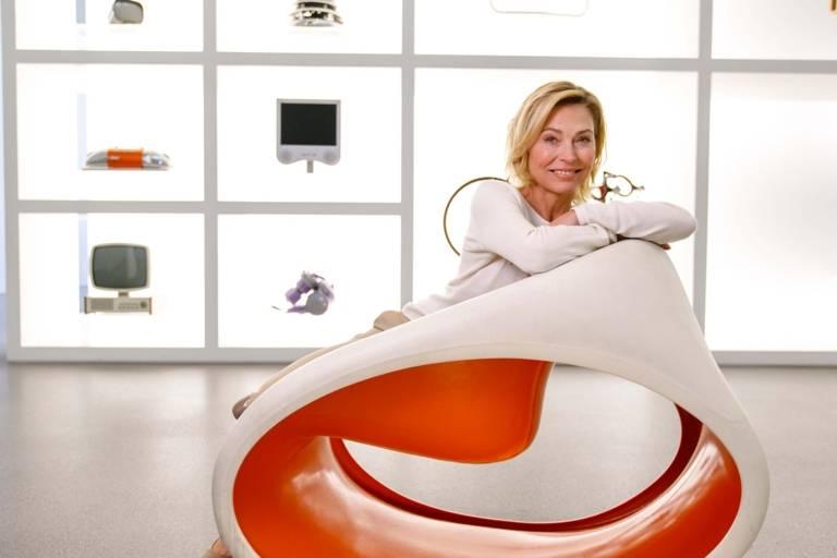 Eine Frau sitzt vor dem Schaukasten der Neuen Sammlung in der Pinakothek der Moderne in München.