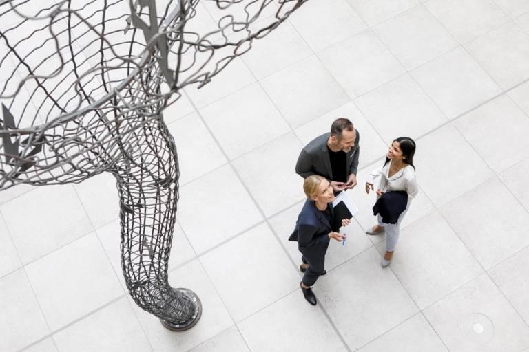 Zwei Frauen und ein Mann erhalten sich neben einer großen Skulpur in Munich.