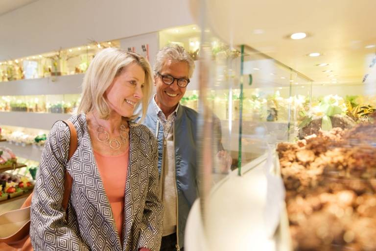 A couple is eyeing chocolate in a vitrine in a shop in Munich.