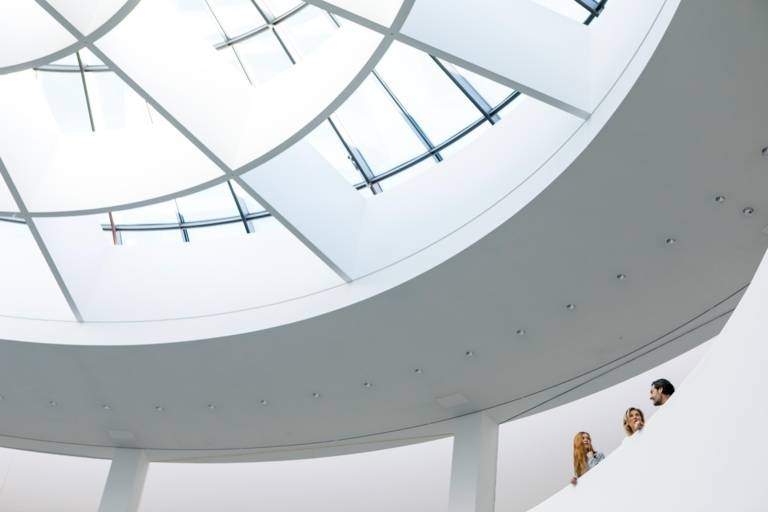 A family is standing in the highest floor of the Pinakothek der Moderne in Munich and is talking to each other.