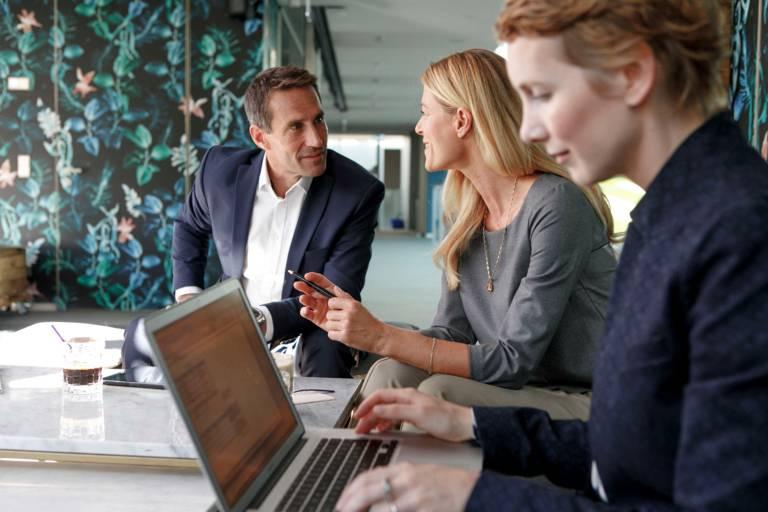 Zwei Frauen und ein Mann sitzen an einem Tisch mit Laptop in einem Münchner Hotel.