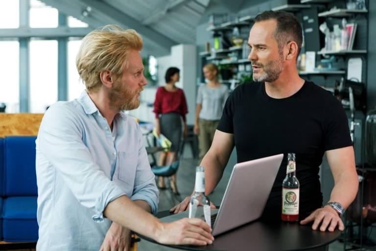 Nahaufnahme von zwei Männern an einem Tisch mit Laptop in München.