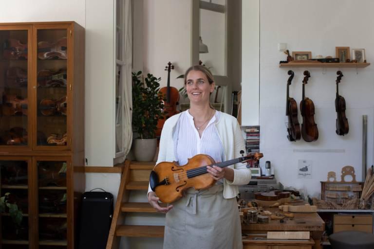 Die Geigenbauerin Katharina Starzer steht in ihrer Werkstatt mit einer Geige in den Händen