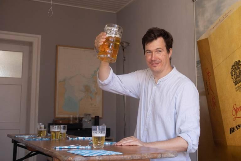 Unser Autor sitzt an der Bierbank in seiner Wohnung in München und trinkt ein Bier