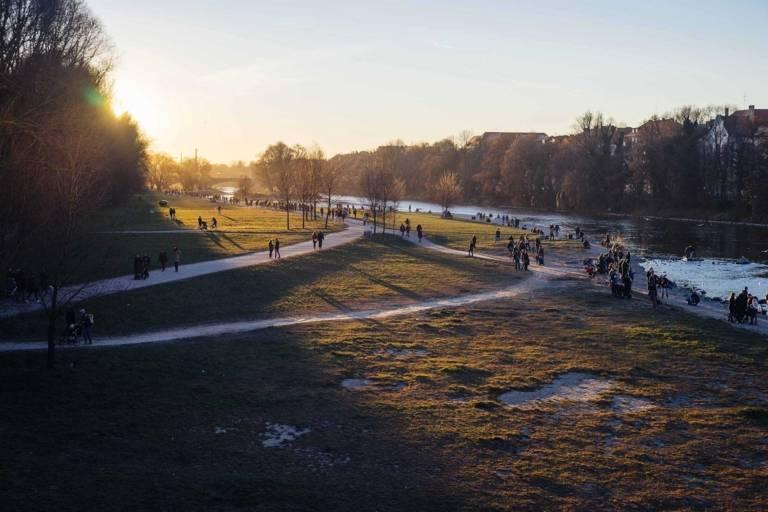 Menschen im Sonnenschein am Flussbett im Winter