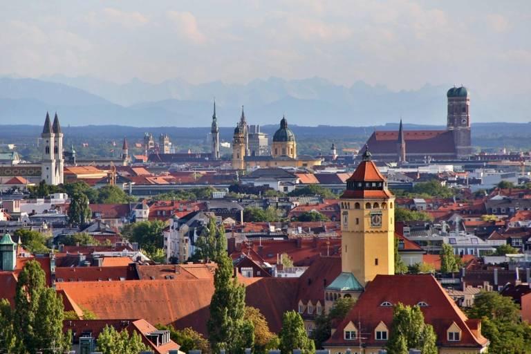 Stadtpanorama von München unter anderem mit den Türmen von Frauenkirche, im Hintergrund die Alpen.