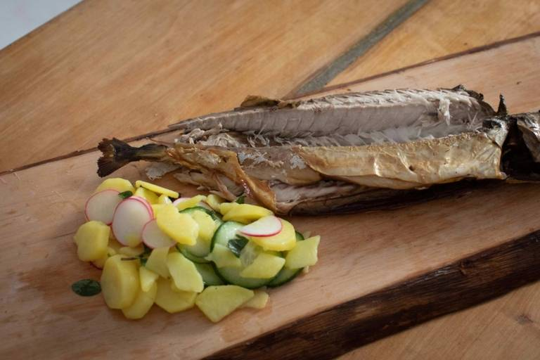 A portion of fish with potato salad, nicely arranged on a wooden board.