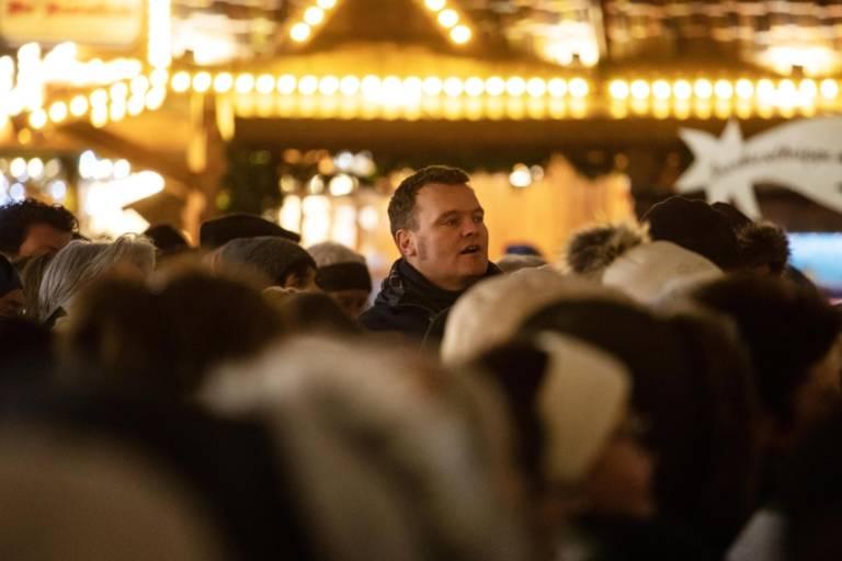 Besucher des Christkindlmarkts bei festlicher Beleuchtung.