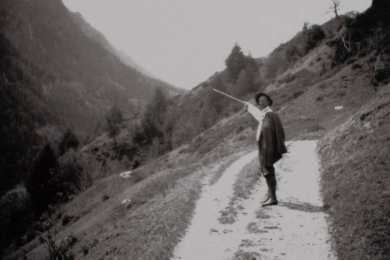 Foto einer schwarz-weiß Aufnahme, auf der ein Mann mit Hut in den Bergen spazieren geht.