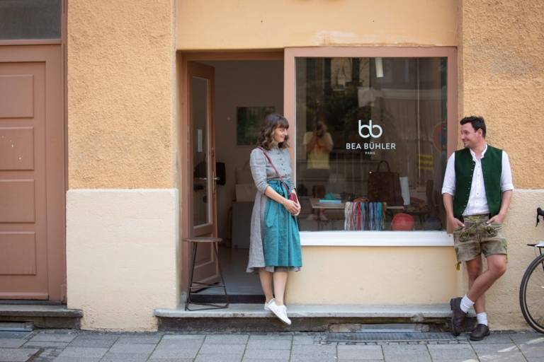 Eine Frau und ein Mann in Tracht stehen vor einem Ladengeschäft