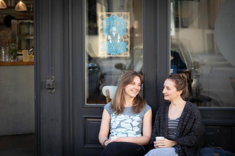 Stephanie Bjarnason und Anika Landsteiner sitzen vor einem Café.
