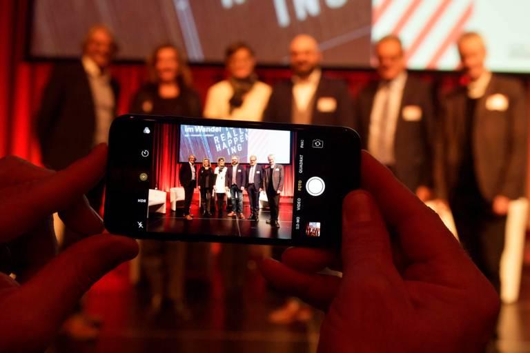 Ein Smartphone fotografiert Menschen auf einer Bühne beim Tourismustag in München