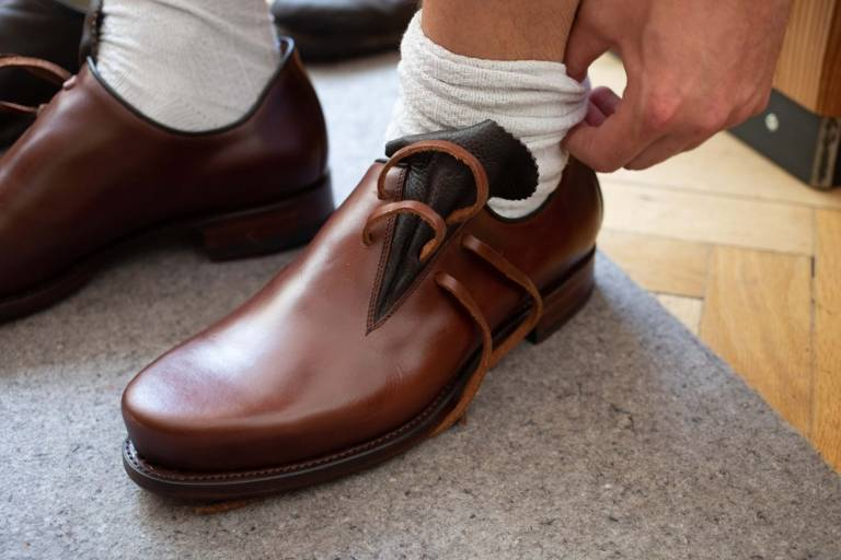 Ein Mann probiert einen braunen Trachtenschuh aus Leder an