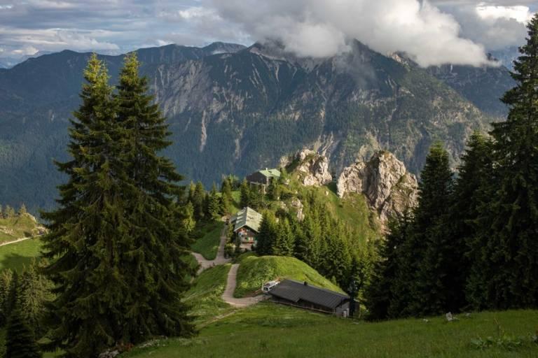Blick auf eine Alpenhütte vor Bergpanorama in München.