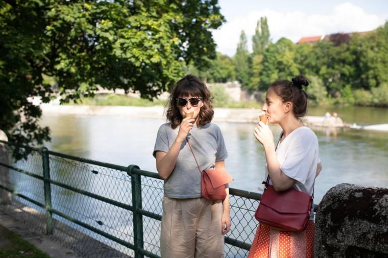 Zwei Frauen essen Eis an der Isar in München.