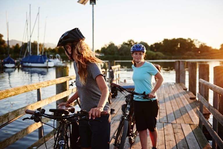 Zwei Frauen mit Fahrrad auf einem Steg an einem See in Bayern.