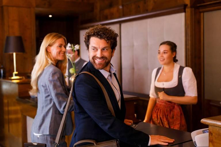 Eine Frau im Dirndl begrüßt eine Frau und einen Mann in einem Hotel in München.
