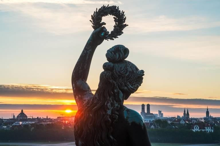 Die Bavaria bei Sonnenaufgang mit der Stadt im Hintergrund