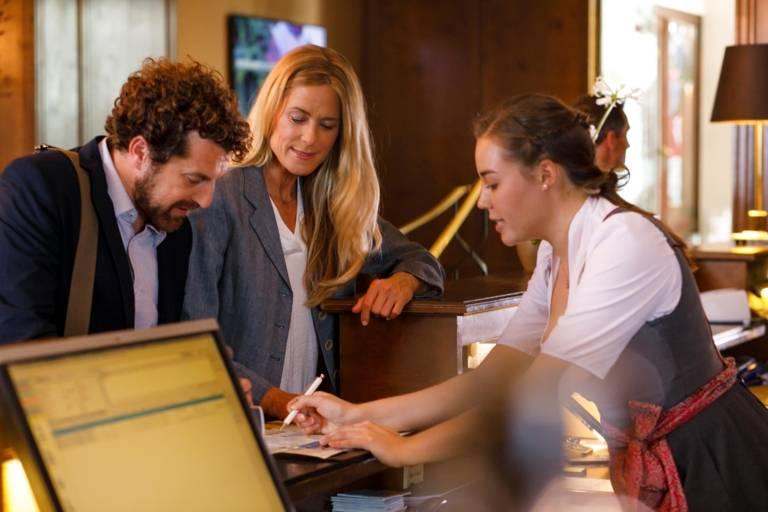 Ein Mann und eine Frau checken in einem Hotel in München ein.