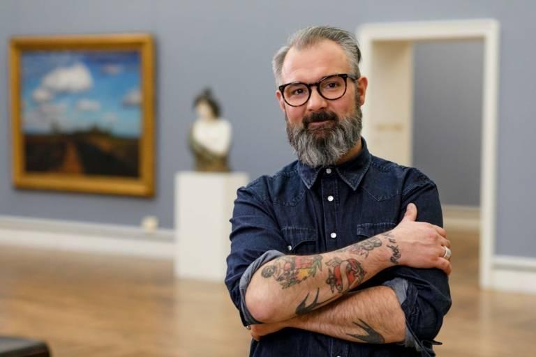 Ein Mann mit Vollbart, Brille und tätowierten Unterarmen in der Neuen Pinakothek in München.