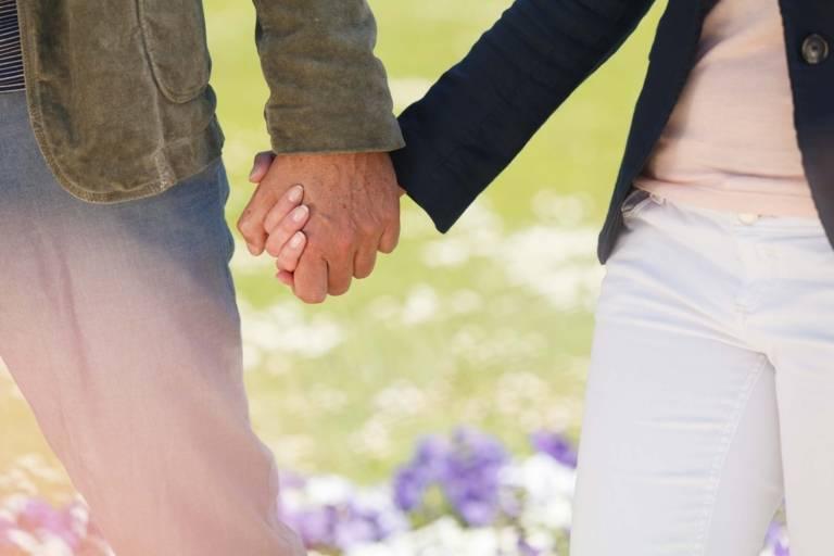Ein Paar läuft Hand in Hand durch den Park des Schloss Nymphenburg in München.