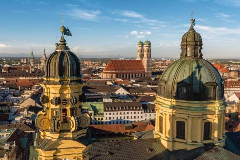 Stadtpanoramablick auf Theatinerkirche, Frauenkirche und Alpen im Hintergrund.