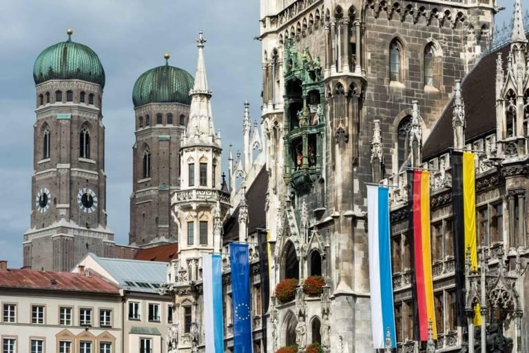 Fahnen vor dem Neuen Rathaus in München, im Hintergrund die Türme der Frauenkirche.