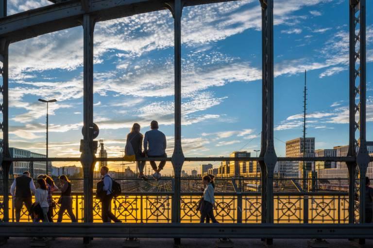 2 Menschen sitzen auf der Hackerbrücke bei Sonnenuntergang in München