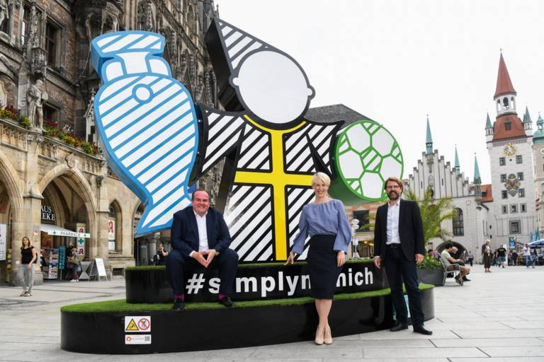 Sportreferent Florian Kraus, Bürgermeisterin Katrin Habenschaden und Clemens Baumgärtner, Referent für Arbeit und Wirtschaft stehen vor dem Spectacular am Marienplatz.