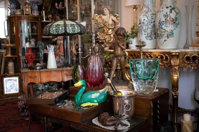 Antike Statuen und Vasen stehen inmitten von Antikmöbeln und alten Lampen