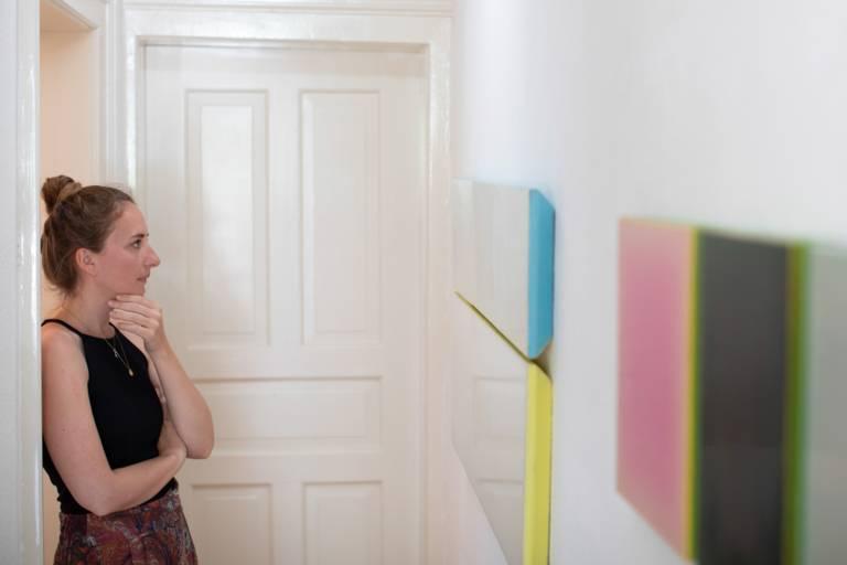 Eine junge Frau betrachtet Bilder in einer Galerie in München.