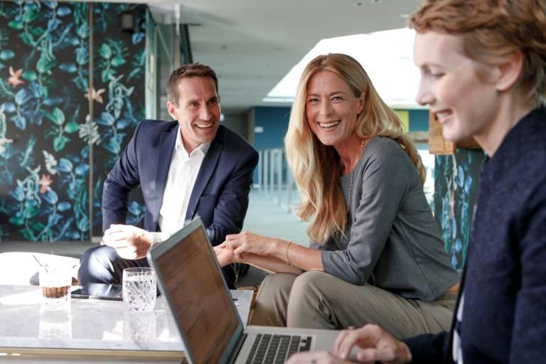 Ein Mann und zwei Frauen sitzen in einem Hotel in München mit einem Laptop.