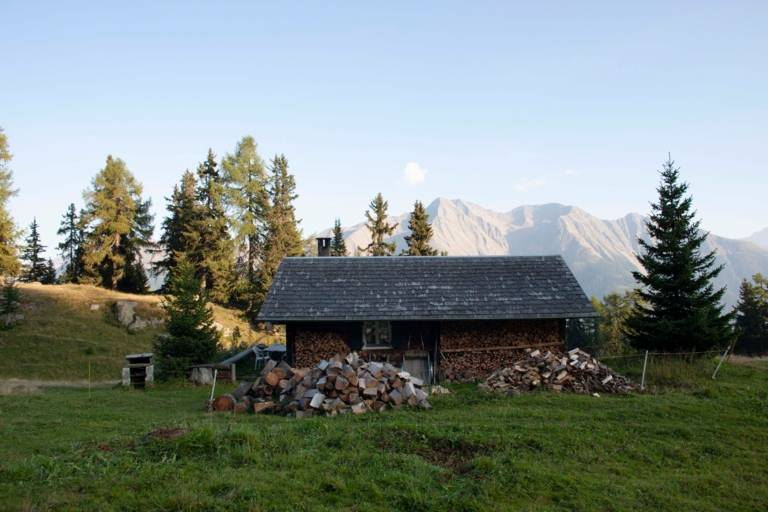 A wooden hut for storing firewood on a meadow in the mountains.