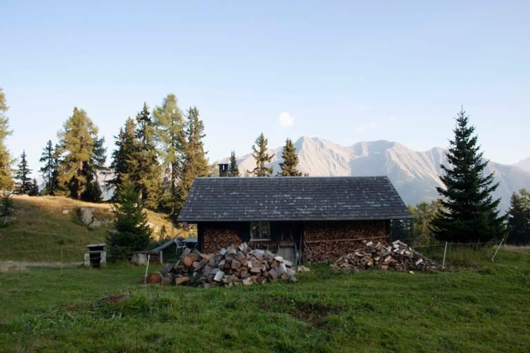 Eine Holzhütte zur Unterbringung von Brennholz auf einer Wiese in den Bergen.