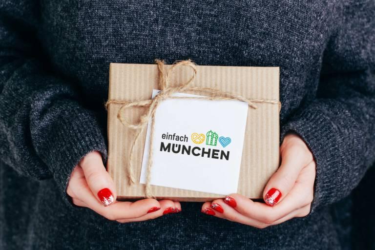 """Eine Frau mit lackierten Fingernägeln hält ein Geschenk mit der Aufschrift """"einfach München"""""""
