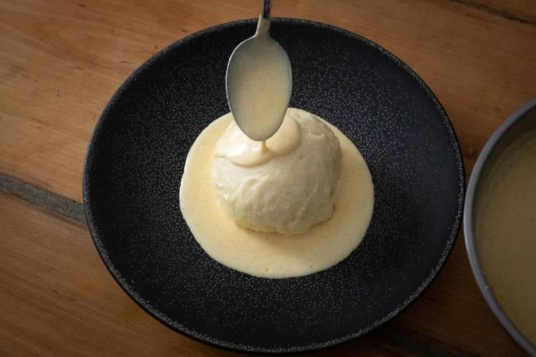 Eine Dampfnudel mit Vanillesoße auf einem dunklen Teller.
